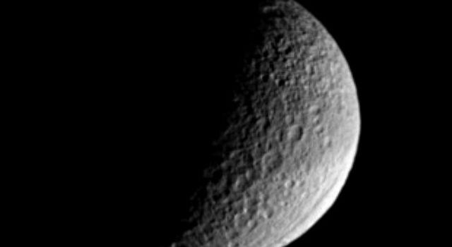 Saturn's moon Tethys, named for a sea goddess, shows off two of its more puzzling features in this image from NASA's Cassini spacecraft. Ithaca Chasma, near lower right, stretches for more than 1,000 kilometers (620 miles) across the moon's surface.