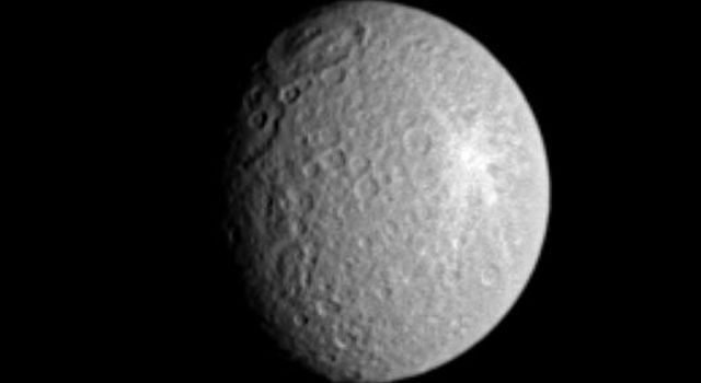 Saturn's moon Rhea displays two large impact features here, along the terminator (the boundary between day and night), plus a superb rayed crater to the east. This image was taken in visible light with NASA's Cassini spacecraft's narrow-angle camera.