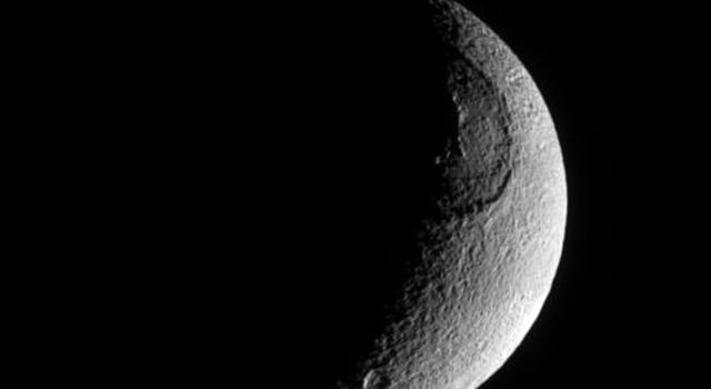 This richly textured look at Saturn's moon Tethys from NASA's Cassini spacecraft shows the huge crater Odysseus and its central mountain in relief, as well as many smaller impact sites.