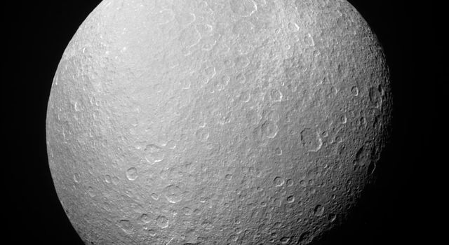 NASA's Cassini spacecraft looks upward at the south polar region on Rhea during a recent distant encounter. Rhea's icy surface is so heavily saturated with impact craters that the moon's limb, or edge, has a rugged, bumpy appearance.