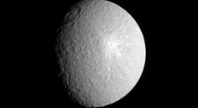The giant Tirawa impact basin straddles the day and night boundary on Saturn's moon Rhea in this view from NASA's Cassini spacecraft.