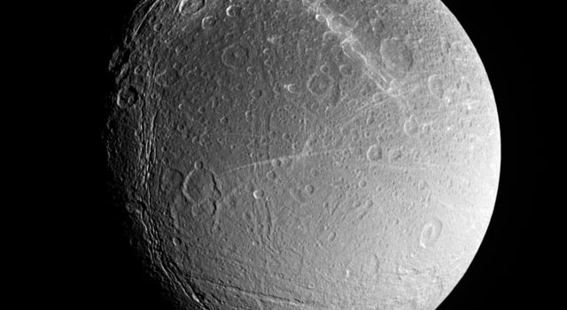 Dione's southern polar region contains fractures whose softened appearance suggests that they have different ages than the bright braided fractures seen in the image to the north. This image was taken with NASA's Cassini spacecraft on Aug. 1, 2005.