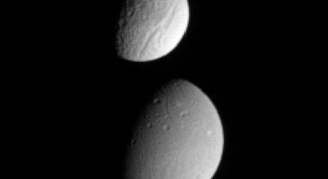 This image from NASA's Cassini spacecraft shows Saturn's moon Tethys partially occulting the moon Dione. The difference in the surface brightness of the two moons is immediately apparent.