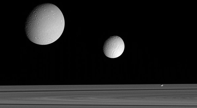 This excellent grouping of three moons Dione, Tethys and Pandora near the rings provides a sampling of the diversity of worlds that exists in Saturn's realm. This image was taken in visible blue light with NASA's Cassini spacecraft's narrow-angle camera.