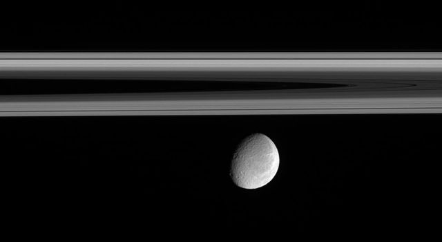 Rhea floats below the innermost regions of Saturn's amazing rings in this image from NASA's Cassini spacecraft. This view of the Saturn-facing hemisphere of Rhea allows a glimpse of the wispy terrain that covers the trailing hemisphere of Rhea.