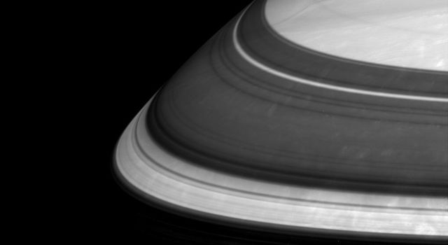 Saturn's rings throw imposing shadows and relegate parts of the planet's northern regions to darkness. Three thin and bright arcs in this scene captured by NASA's Cassini spacecraft represent three well-known gaps in the immense ring system.