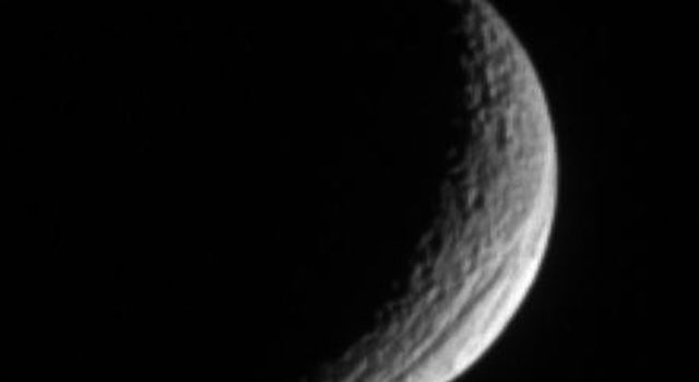 A crescent Tethys shows off its great scar, Ithaca Chasma, for which the moon is renowned. The lit surface visible here is on the moon's Saturn-facing hemisphere. This image is from NASA's Cassini spacecraft.