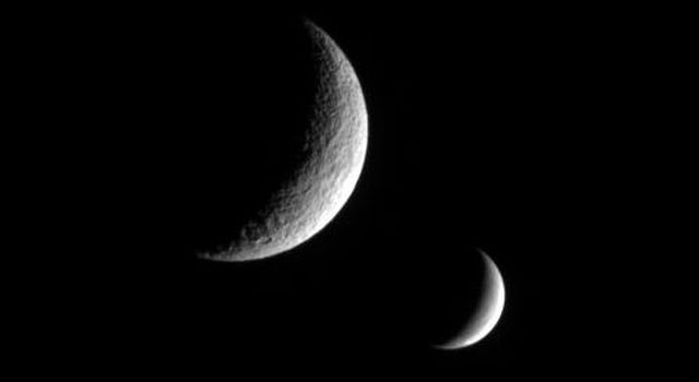 NASA's Cassini spacecraft captures this dual portrait of an apparently dead moon and one that is very much alive. Tethys, shows no signs of recent geologic activity. Enceladus is covered in fractures and faults and spews icy particles into space.