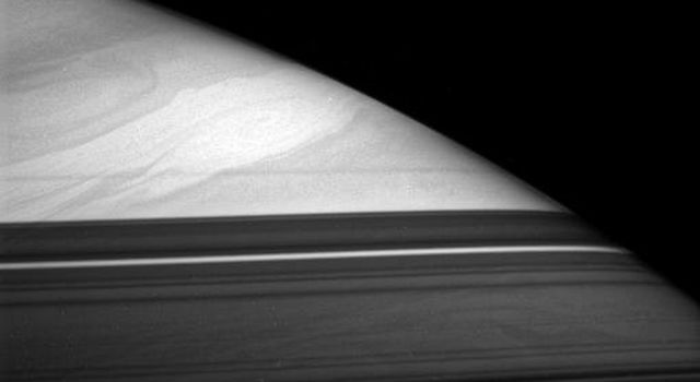 A great storm swims in the cloud lanes of Saturn's high northern latitudes. Dark bands across the bottom of this view from NASA's Cassini spacecraft are shadows cast by the partly opaque rings.