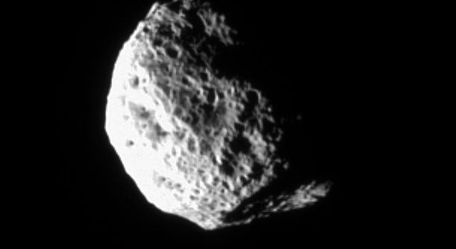 The tumbling and irregularly shaped moon Hyperion rotates away from NASA's Cassini spacecraft in this image taken during a distant encounter on Dec. 23, 2005. Hyperion (174 miles across) is covered with closely packed and deeply etched pits.