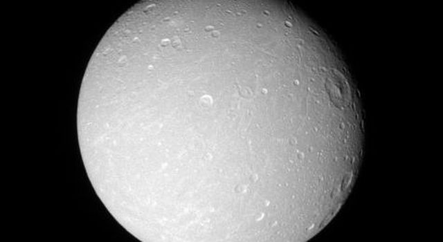 The leading hemisphere of Saturn's moon Dione displays linear grooves and subtle streaks in this image taken with NASA's Cassini spacecraft's narrow-angle camera on Dec. 24, 2005.