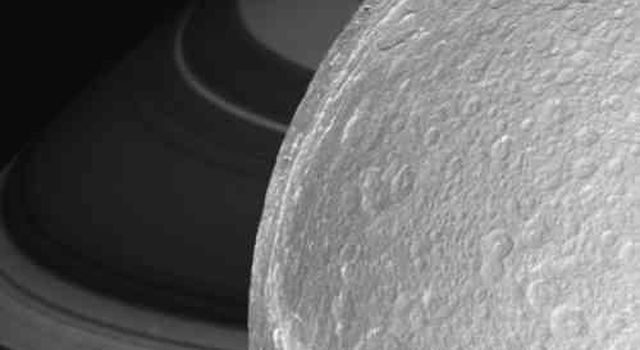 Zooming in closer and closer, this frame from a movie chronicles NASA's Cassini spacecraft targeted flyby of Dione, with Saturn and its lovely rings forming a dramatic backdrop.