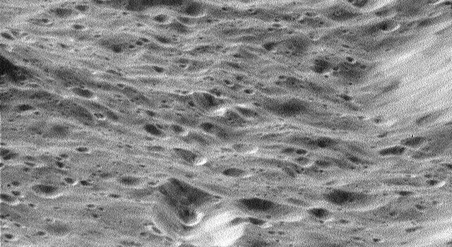 This image from NASA's Cassini spacecraft shows craters within craters cover the scarred face of Saturn's moon Rhea in this oblique, high-resolution view of terrain on the moon's western hemisphere.