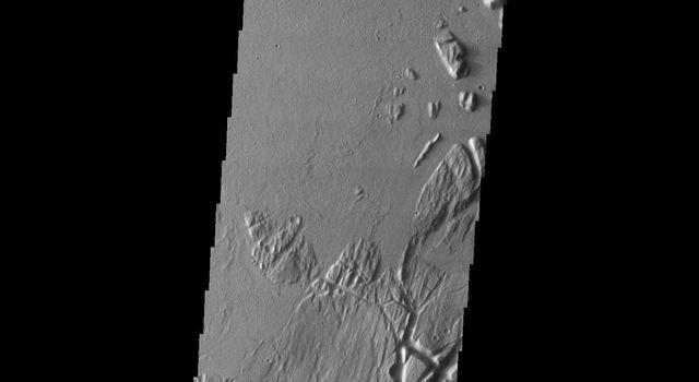 This image taken by NASA's Mars Odyssey shows the eastern part of the Tharsis region on Mars; fractured materials on the right are embayed by younger volcanic flows originating to the west.
