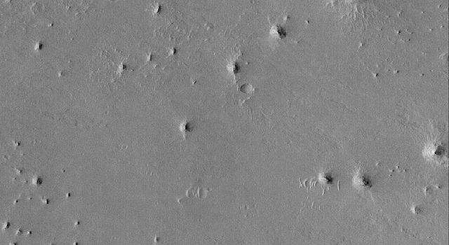 NASA's Mars Global Surveyor shows buttes and two eroded impact craters on the plains west of Sinus Meridiani on Mars. The layers can be seen in the walls of the two large, dark-floored craters.