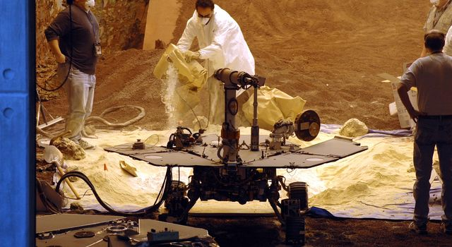 Rover engineers prepare a mixture of sandy and powdery materials to simulate some difficult Mars driving conditions inside a facility at NASA's Jet Propulsion Laboratory, Pasadena, Calif.