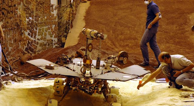 Rover engineers check how a test rover moves in material chosen to simulate some difficult Mars driving conditions. The scene is inside the In-Situ Instrument Laboratory at NASA's Jet Propulsion Laboratory, Pasadena, Calif.