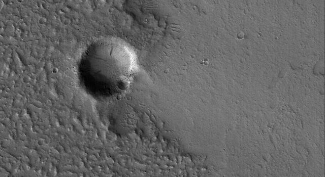 This NASA Mars Global Surveyor image shows the margin of an ancient, cratered, hummocky (rough) lava flow at just the point where it encroached upon a small impact crater east of the volcano, Tharsis Tholus.