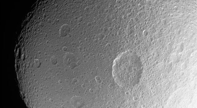 This dramatic close-up from NASA's Cassini spacecraft of Saturn's moon Tethys shows the large crater Penelope lying near center, overprinted by many smaller, younger impact sites.