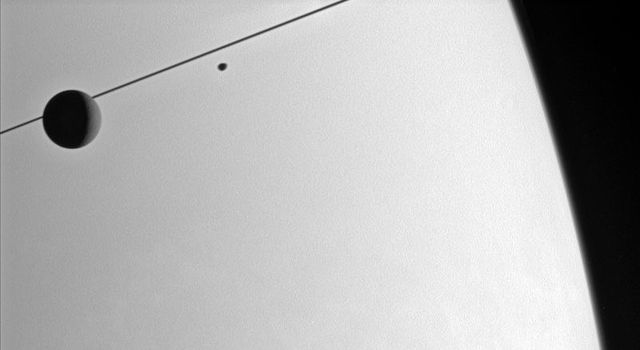NASA's Cassini spacecraft looks toward the Saturnian horizon as Dione and Janus glide past.