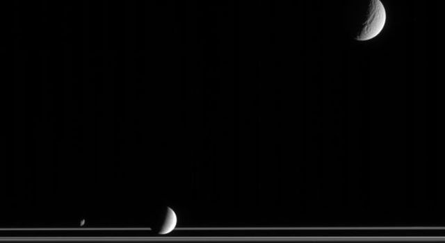 The three very different moons seen here provide targets of great interest for planetary scientists studying the Saturn system. Captured by NASA's Cassini, along with the rings, are Tethys at upper right, Enceladus below center and Janus at lower left.