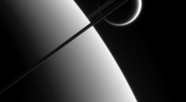This view was taken from above the ringplane and looks toward the unlit side of the rings. Here, the probe gazes upon Titan in the distance beyond Saturn and its dark and graceful rings as seen by NASA's Cassini spacecraft.