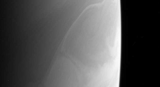 Saturn's atmosphere produces beautiful and sometimes perplexing features. The bright feature below center may be a rare crossing of a feature from a zone to a belt, as seen by NASA's Cassini spacecraft.