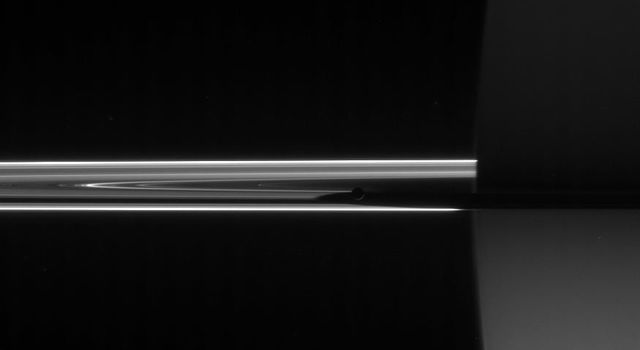 NASA's Cassini spacecraft looked toward the night side of Saturn to spy the darkened orb of Mimas barely visible here near the center of the image hugging the planet's shadow.