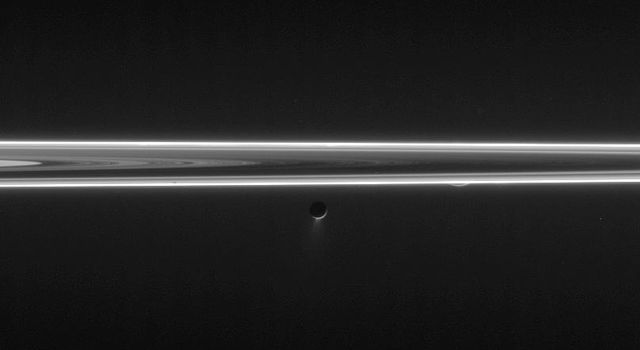 Enceladus blasts its icy spray into space in this unlit-side ring view that also features a tiny sliver of Rhea. This image was taken in visible light with NASA's Cassini spacecraft's narrow-angle camera on June 9, 2006.