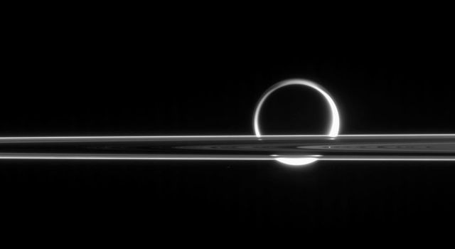 Titan shines beyond the rings like a brilliant ring of fire, its light gleaming here and there through the gaps in Saturn's magnificent plane of ice. This image was taken in visible light with NASA's Cassini spacecraft's narrow-angle camera.