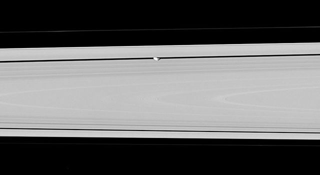 Hiding within the Encke gap is the small moon Pan, partly in shadow and party cut off by the outer A ring in this view. Similar to Atlas, Pan appears to have a slight ridge around its middle; and like Atlas, Pan's orbit also coincides with a faint ringlet
