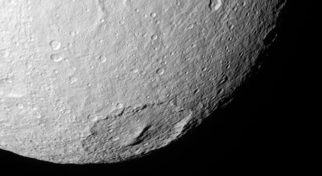 NASA's Cassini spacecraft looks into the wide crater Melanthius in this view of the southern terrain on Saturn's moon Tethys. The crater possesses a prominent cluster of peaks in its center which are relics of its formation.