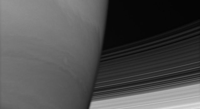 Saturn's B and C rings disappear behind the immense planet. Where they meet the limb, the rings appear to bend slightly owing to upper-atmospheric refraction as seen by NASA's Cassini spacecraft.