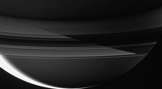 Saturn's shadow cuts sharply across the rings in this remarkable night side view captured by NASA's Cassini spacecraft.