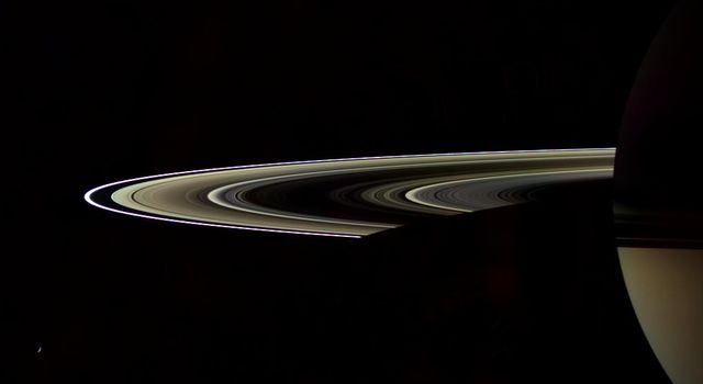 Sunlight filters through Saturn's rings in sepia tones in this artful view from NASA's Cassini spacecraft of the dark side of the rings.