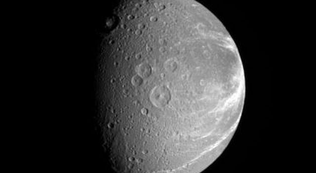 Bright fractures creep across the surface of icy Dione. This extensive canyon system is centered on a region of terrain that is significantly darker that the rest of the moon in this image captured by NASA's Cassini spacecraft on Sept. 27, 2006.