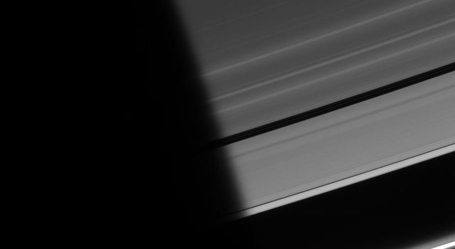As ring particles emerge from the darkness of Saturn's shadow, they pass through a region of twilight. The Sun's light, refracted by the planet's atmosphere, peeks around the limb, followed shortly by the Sun itself as seen by NASA's Cassini spacecraft.