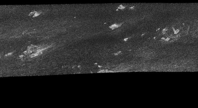 "This image was taken with NASA's Cassini Synthetic Aperture Radar instrument on Oct. 28, 2005. This was the fourth flyby of Titan during which radar images were obtained. The most ubiquitous features in this swath are ""cat scratches.'"
