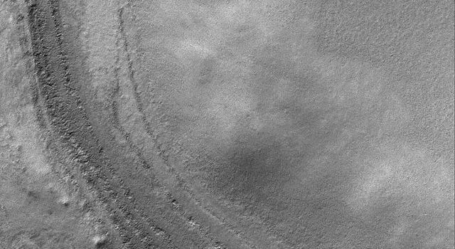 NASA's Mars Global Surveyor shows remnants of layered materials near the west rim of South Crater, Mars. The composition of these layered rocks is unknown -- are they the remains of sedimentary rocks or accumulations of dust and ice?