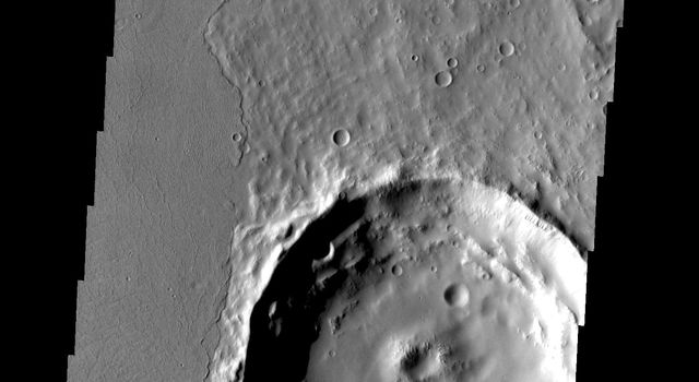Located on the eastern edge of the Tharsis region on Mars, this crater has had half of its ejecta covered by lava flows as seen by NASA's 2001 Mars Odyssey.