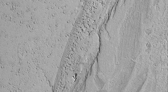 NASA's Mars Global Surveyor shows a variety of textures observed on a dust-covered plain in the Marte Valles region of Mars.