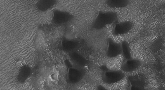 NASA's Mars Global Surveyor shows dark sand dunes on the floor of an impact crater west of Hellas Planitia on Mars. Portions of the crater floor are exposed near the center but, in general, the floor is covered by large, windblown ripples.