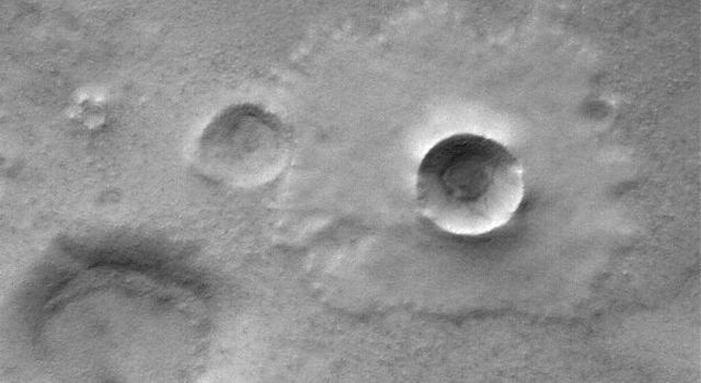 This image from NASA's Mars Global Surveyor shows a pedestal crater superposed on the floor of the much larger Mellish Crater. When an impact crater of this type forms, material is thrown onto the adjacent terrain to form portions of the ejecta blanket.