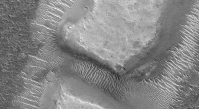 NASA's Mars Global Surveyor shows blocky remnants of a material that was once more laterally extensive on the floor of an impact crater located NW of Herschel Crater. Large ripples of windblown sediment have accumulated around and between the blocks.