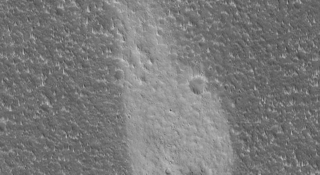 NASA's Mars Global Surveyor shows a light-toned wind streak created in the lee, downwind side, of an impact crater in the Cyane Fossae region of Mars.