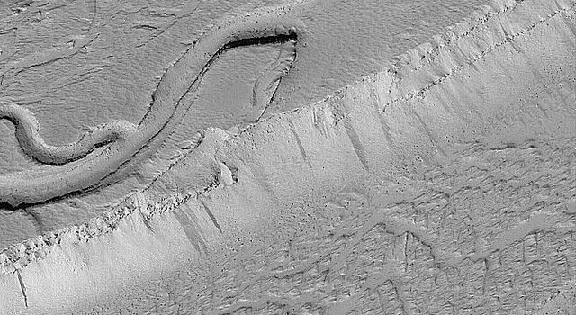 NASA's Mars Global Surveyor shows a wide, flat-floored trough flanked by several smaller, branching troughs in the Olympica Fossae region of Mars. Dark- and intermediate-toned slope streaks, created by dry avalanches of dust, occur on the trough walls.