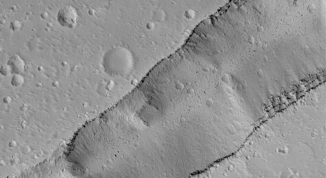 NASA's Mars Global Surveyor shows a portion of a trough cutting across a dust-covered plain in the Labeatis Fossae region of Mars. Boulders derived from the layered exposures near the top of the trough walls are resting on the floor.