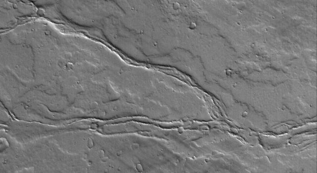 NASA's Mars Global Surveyor shows the remains of leveed lava channels cutting across (west to east) a dust-covered plain composed of overlapping lava flows east of Olympus Mons on Mars.