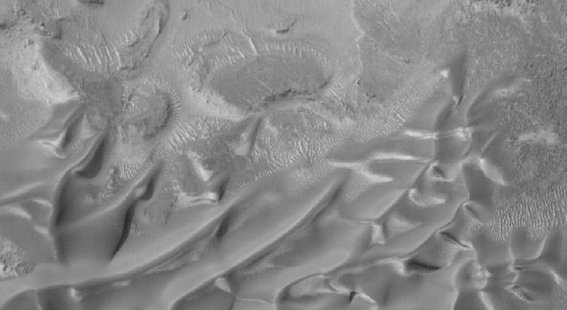 NASA's Mars Global Surveyor shows gullies overlain by seasonal frost in the north wall of an unnamed crater west of Hellas Planitia on Mars.