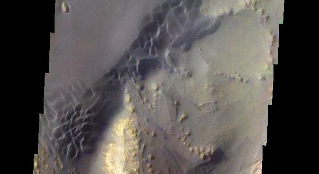 This image from NASA's 2001 Mars Odyssey shows the sand dunes and layered material common on the floor of Valles Marineris.